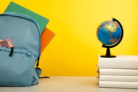 Blue backpack with school supplies with globe on books. Back to school concept