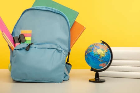 School supplies and globe on a table isolated on yellow.