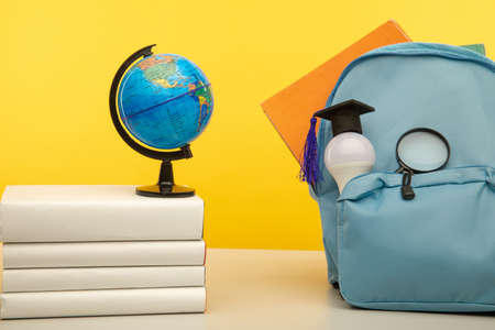 Blue school backpack, globe and bulb on a table