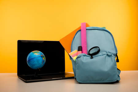 School backpack with supplies and laptop on a table. Online education concept