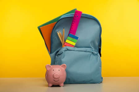 Backpack with school tools and piggy bank on yellow background 版權商用圖片