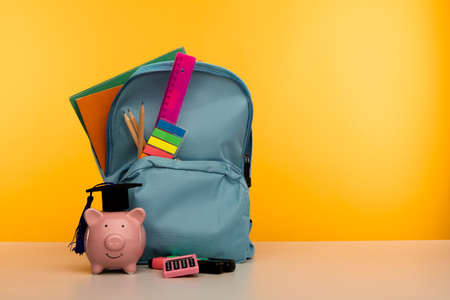 Blue backpack with school tools and piggy bank in hat on yellow background