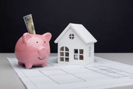 Model of house and piggy bank with dollar on architectural plan. House building costs