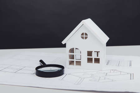 Magnifier glass, white house and paper part of architectural plan. Real estate building concept