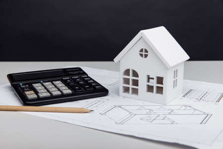White house and calculator on drawing. House building estimate concept 版權商用圖片