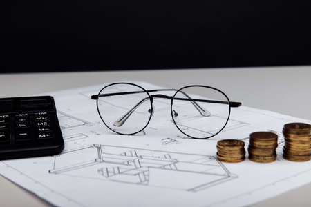 Drawing, glasses and calculator with coins. Building cost concept