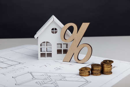 Model of house and symbol of percent with coins on architectural plan. Building investment