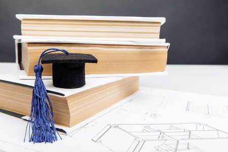 Technical drawings and graduation cap with books. Engineering education concept