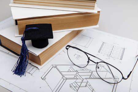 Technical drawings and graduation hat on books. Engineering education concept. Top view