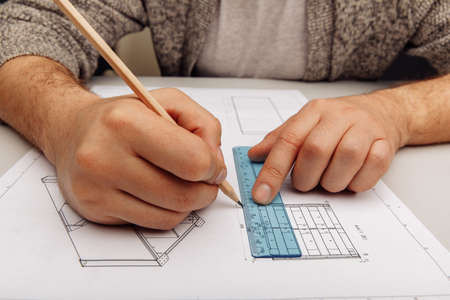 Male engineer works with blueprints laying on a table, using pencil