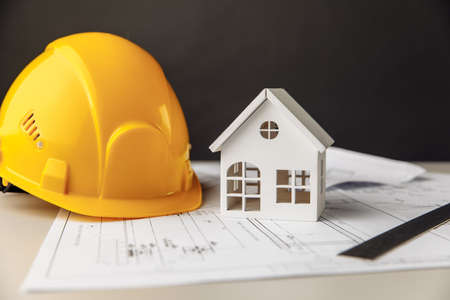 Construction plans with helmet and model of house