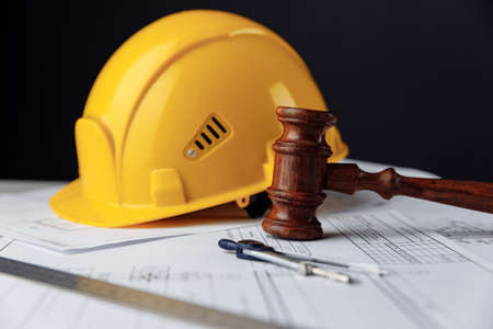 Wooden gavel with yellow helmet. Construction law concept
