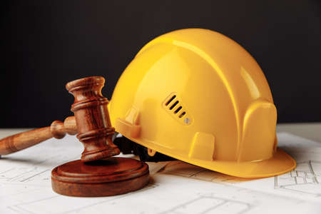 Wooden gavel with yellow helmet close-up. Construction law theme
