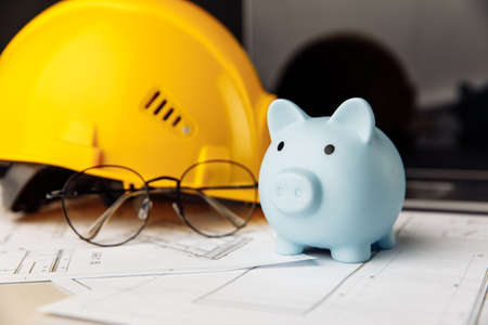 Yellow safety helmet and piggy bank with blueprint, glasses and laptop on table 版權商用圖片