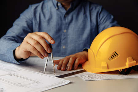 Architects workplace with helmet and drawing tools. Man working on blueprint