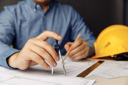 Engineers workplace with yellow helmet and drawing tools. Man working on blueprint