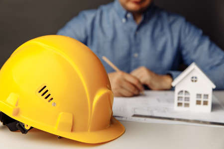 Construction concept. Architect working on blueprint, yellow helmet in focus