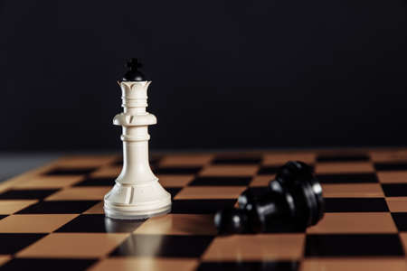 White king standing and falling on chessboard with black background 版權商用圖片