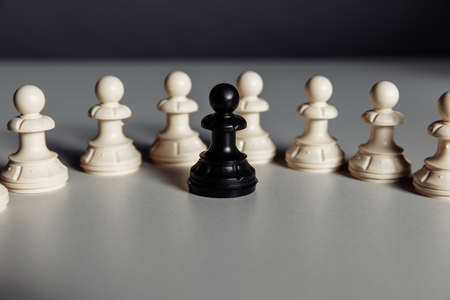 Leadership and business concept, black pawn of chess standing out from the crowd of white