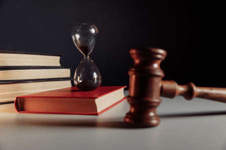 Hourglass with red book and judge gavel close-up