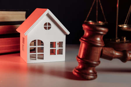 Sale of real property concept. Wooden model of house and judge gavel close-up 版權商用圖片