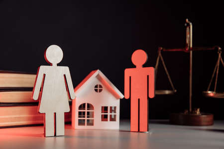 Wooden model of couple and house in notary office. Law and divorce concept 版權商用圖片