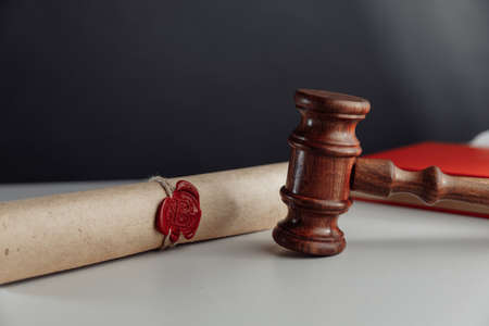 Gavel and document with wax seal on a lawyers desk