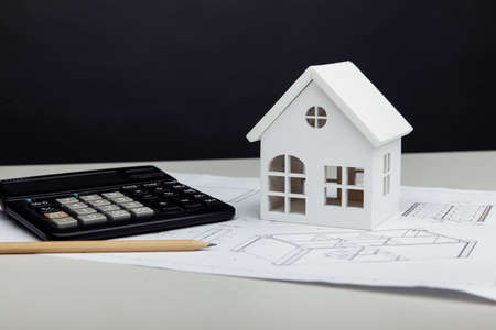 White house and calculator on architectural project. House building costs concept