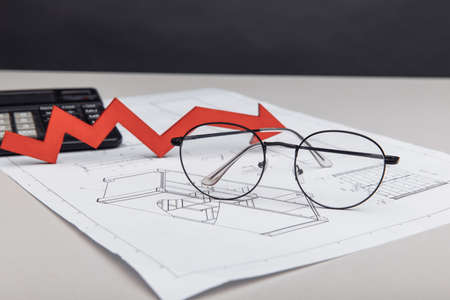 Financial and trading concept. Calculator, glasses and arrow up on architectural project