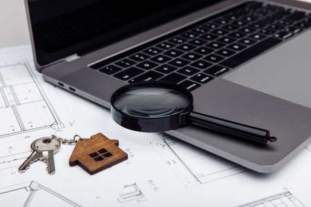 House key, laptop and a magnifying glass on a drawing. Real estate construction concept