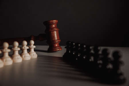 Chess pieces and law gavel isolated on a dark background