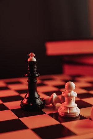 Black king standing on chessboard around falling pawns. Leadership concept. Vertical image 版權商用圖片