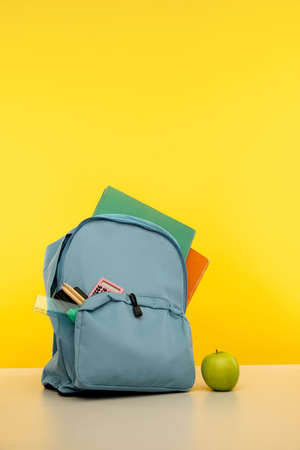 Blue backpack with different colorful stationery on table. Banner design. Vertical image 版權商用圖片