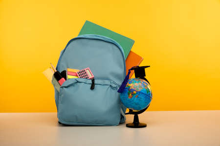 Back to school theme. Backpack with school supplies with globe on yellow background