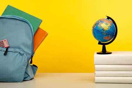 Blue backpack for education children on yellow background. Back to school concept