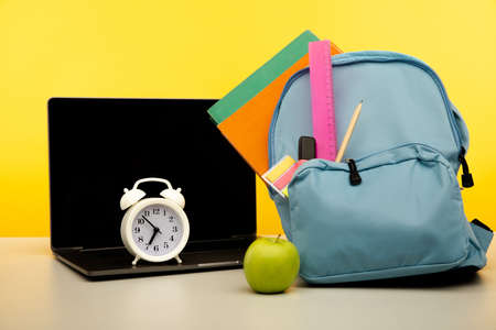 Bright backpack with supplies and laptop on a table. Online education theme