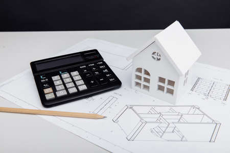 Model of house and calculator on architectural plan. House building costs 版權商用圖片