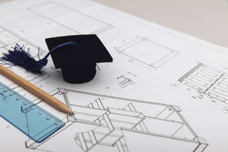 Mechanical drawings and graduation cap close-up. Engineering education concept