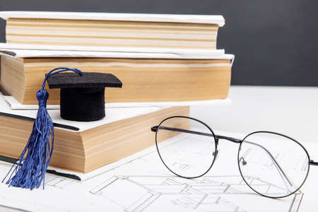 Technical project, glasses and graduation cap with books. Engineering education concept 版權商用圖片