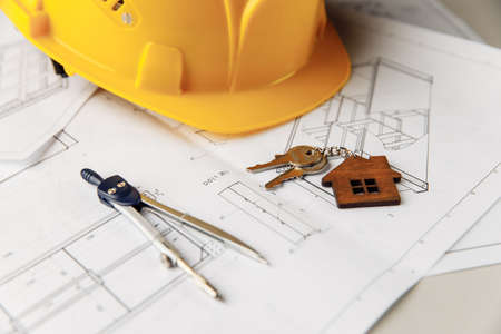 Construction plans with yellow helmet, house keys and drawing tools on a table close-up