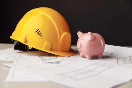 Construction safety helmet and piggy bank with blueprint 版權商用圖片