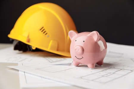 Building costs concept. Yellow safety helmet and pink piggy bank with drawings
