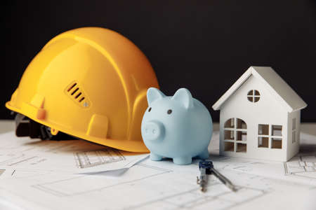 Building concept. Yellow safety helmet and blue piggy bank with drawings and model of house