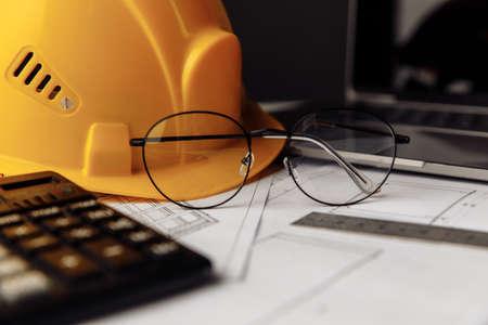 Yellow helmet, glasses and laptop on construction plans close-up 版權商用圖片