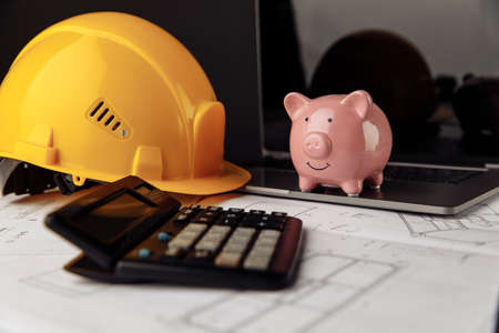 Yellow safety helmet and piggy bank with blueprint, calculator and laptop on table
