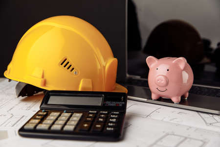 House building costs concept. Safety helmet and piggy bank with blueprint, calculator and laptop on table 版權商用圖片