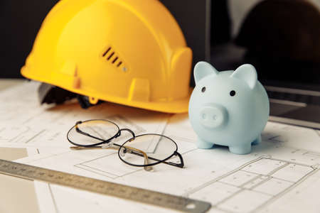 Construction safety helmet and piggy bank with blueprint, glasses and laptop on table. Building theme