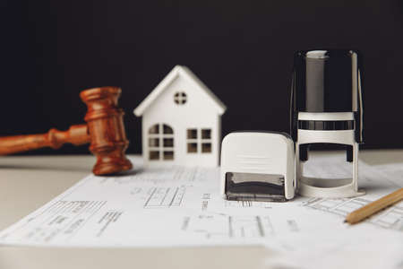 Judge gavel, stamp and model of house with blueprint. Building and law concept 版權商用圖片