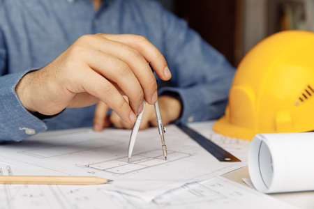 Construction engineer working on blueprint architectural project at desk in office