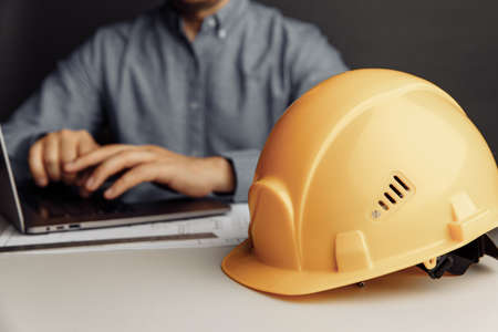 Construction engineer working on laptop. Building theme. Engineers workplace with helmet 版權商用圖片